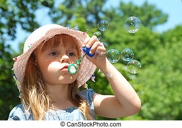 bubble wand - adorable little girl playing with a bubble...