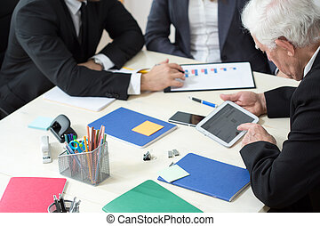 Close-up of working businesspeople sitting at the table