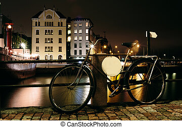 Bicycle at night near the pier on the background of the city...