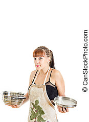 Lovely housewife in apron trying to cook and prepare meal in...