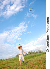 girl playing with a kite - girl running and flying a kite in...