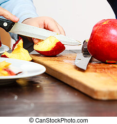 child cut apple with a kitchen knife - Child little boy...