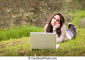 Young beautiful woman using a laptop computer at the park