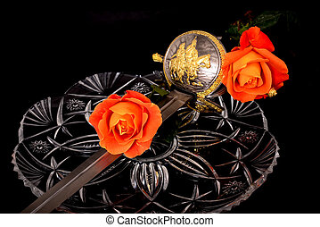 Cutlass and roses isolated over a black background