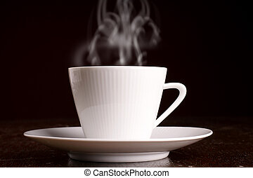 Cup of steaming hot coffee over dark background
