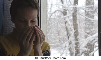 Snow Outside the Window - Young Woman with a cup of hot...