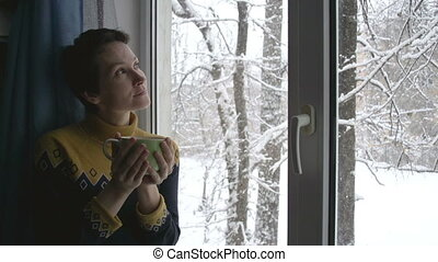 Snow Outside the Window and Hot Tea - Young Woman with a cup...