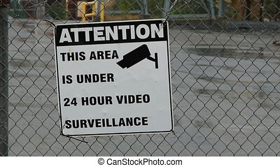 CCTV sign on factory fence Rain falling Sudbury, Ontario