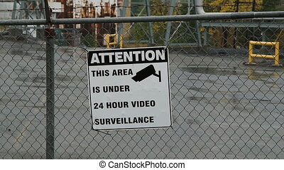 CCTV sign on factory fence. Rain falling. Sudbury, Ontario.