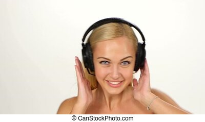 Beautiful female in headphones listening to the music with...