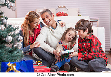 Smiling family of four unwrapping Christmas presents.