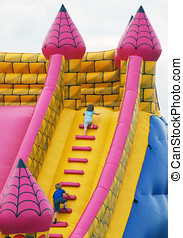 Bumper castle fun - Young children climb steps in inflatable...
