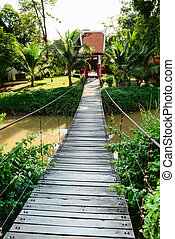 Wooden long rope bridge cross the stream in green tropical...