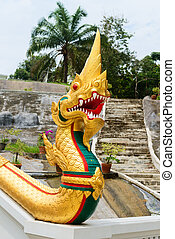 Golden naga snake on entrance of buddhist temple in Thailand