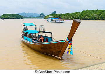 Traditional wooden boat against tropical background -...