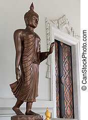 Walking Buddha statue with imparting fearlessness gesture in...