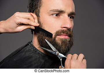 Bearded man - Image as somebody is trimming the beard of a...