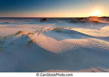 sunrise over sand dunes on North sea beach