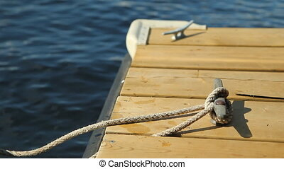 Cleat on wooden dock. - Handheld, stabilized shot of dock...