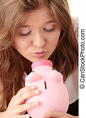 Woman and piggy bank - Young beautiful woman siting at the...