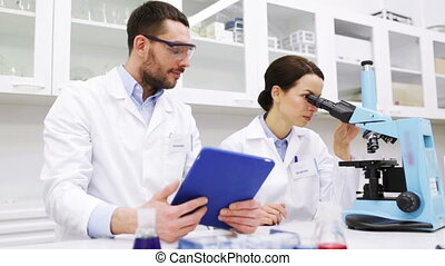 scientists with tablet pc and microscope in lab - science,...