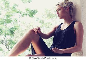 Young woman sitting by golden light