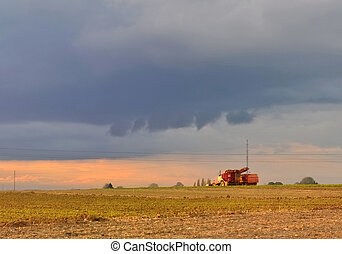 rural scene - tractor in a field under a threatening sky and...