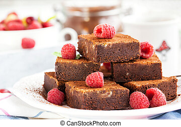 Homemade chocolate brownies decorated with fresh raspberry