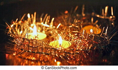 Christmas candles burn among fir-tree tinsel