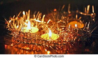 Christmas candles burn among fir-tree tinsel