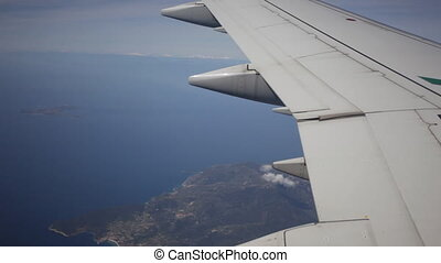 Plane flies by over the sea and the land, a view from a window, in a shot a plane wing