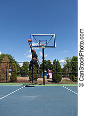 Big Slam Dunk - Young basketball player flying to the hoop...