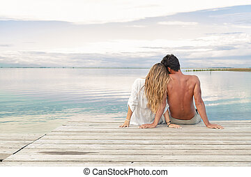 man and woman couple sitting on a Jetty under a blue cloudy...