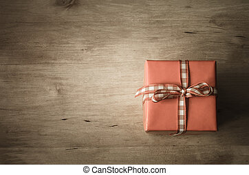 Overhead Gift Box on Wood - A square gift box, tied with...