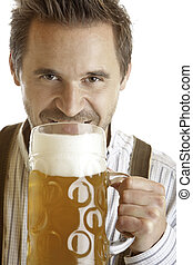 closeup of an Bavarian man which wants to drink out of Oktoberfest beer stein