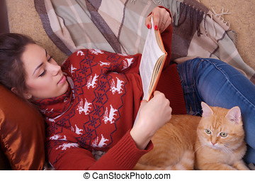 Girl lying on the sofa with red cat and reading a book -...