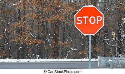 Stop sign on a highway with traffic cars