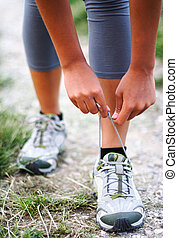 Running shoes being tied by woman getting ready for jogging.