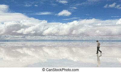 Man talking on the mobile phone in the middle of lake Salar...