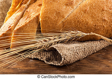 ear of wheat on a background of sliced white bread