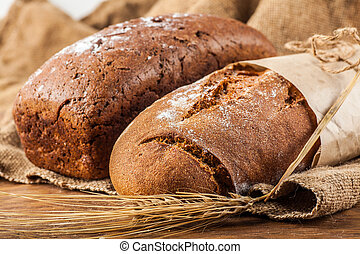 two bread with ears of wheat on the wooden background