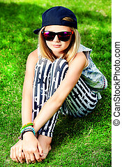enjoy summer - Modern girl teenager sitting on a grass.