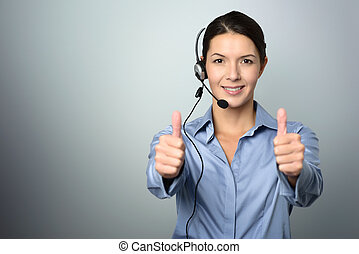 Attractive call center operator giving thumbs up -...
