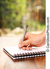 Hand writing on notepad - A hand writing on a notepad on a...