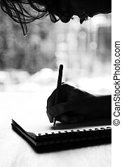 Person writing on notepad - Black and white image of a...