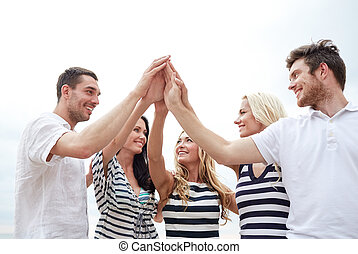 smiling friends making high five gesture outdoors -...