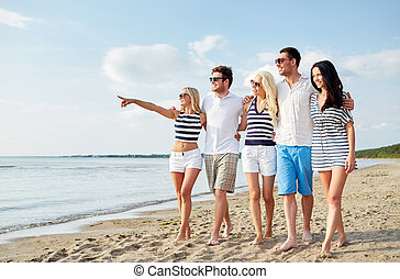 smiling friends in sunglasses walking on beach - summer,...