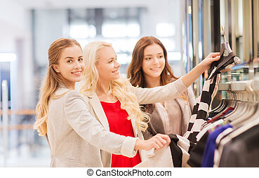 happy young women choosing clothes in mall - sale,...