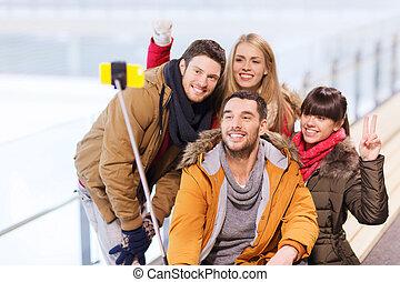 feliz, amigos, con, smartphone, en, patinaje, Pista,
