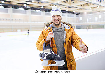 happy young man showing thumbs up on skating rink - people,...